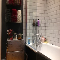 Metro tiles with dark grey grout and glass shower screen.